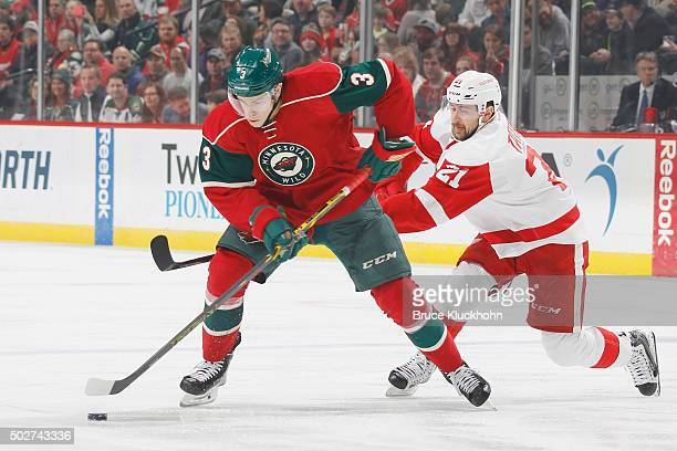 Charlie Coyle of the Minnesota Wild handles the puck with Tomas Tatar of the Detroit Red Wings defending during the game on December 28 2015 at the...