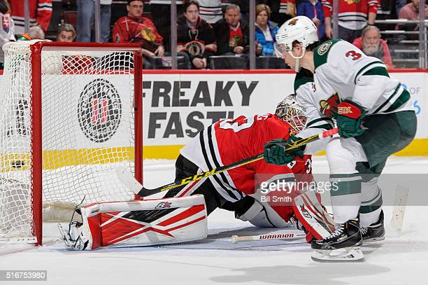 Charlie Coyle of the Minnesota Wild scores the game winning goal against goalie Scott Darling of the Chicago Blackhawks in the shootout of the NHL...