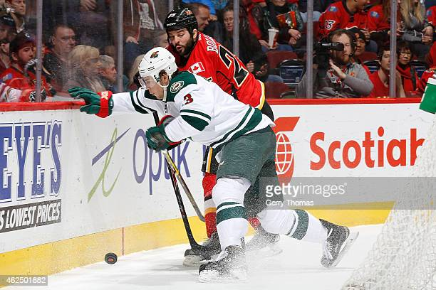 Charlie Coyle of the Minnesota Wild skates against Brandon Bollig of the Calgary Flames at Scotiabank Saddledome on January 29 2015 in Calgary...