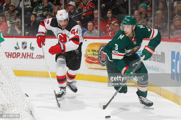 Charlie Coyle of the Minnesota Wild skates with the puck while Miles Wood of the New Jersey Devils defends during the game at the Xcel Energy Center...