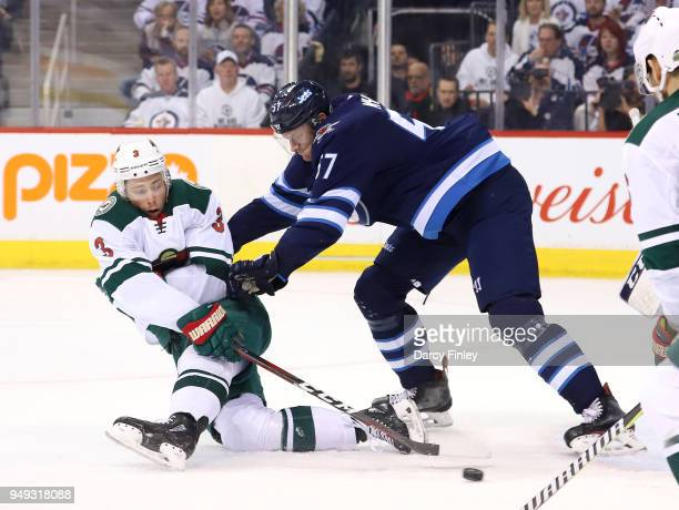 Charlie Coyle of the Minnesota Wild swipes at the puck as he gets knocked to the ice by Tyler Myers of the Winnipeg Jets during second period action...