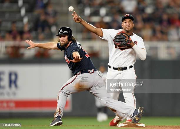 Charlie Culberson of the Atlanta Braves calls himself safe as Jonathan Schoop of the Minnesota Twins attempts to get an out at first base during the...