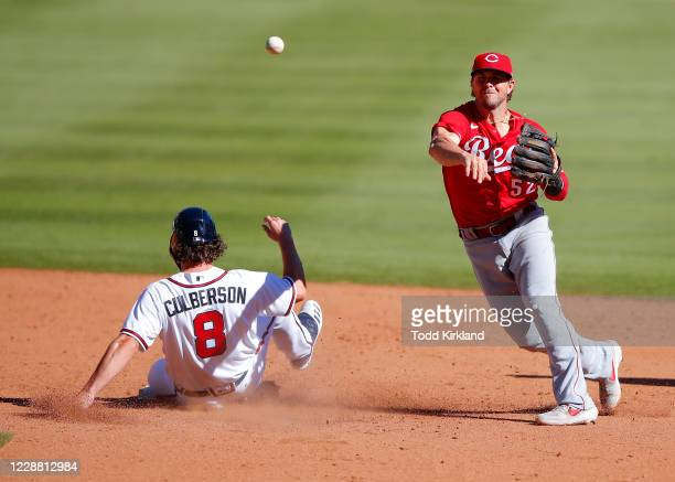 Charlie Culberson of the Atlanta Braves is forced out at second by Kyle Farmer of the Cincinnati Reds in inning twelve of Game One of the National...