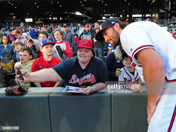 Charlie Culberson of the Atlanta Braves poses with a fan taking a selfie before the game against the New York Mets at SunTrust Park on April 19 2018...