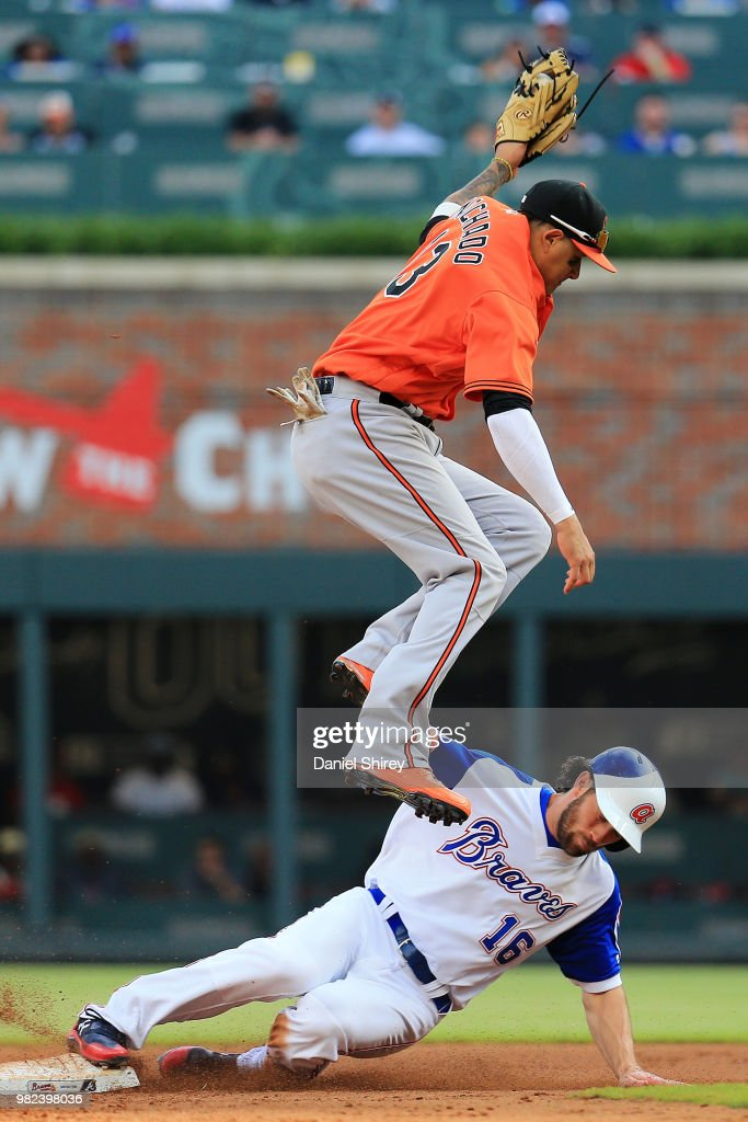 Charlie Culberson #16 of the Atlanta Braves slides underneath Manny Machado #13 of the Baltimore Orioles to safely steal second during the eighth inning at SunTrust Park on June 23, 2018 in Atlanta, Georgia.