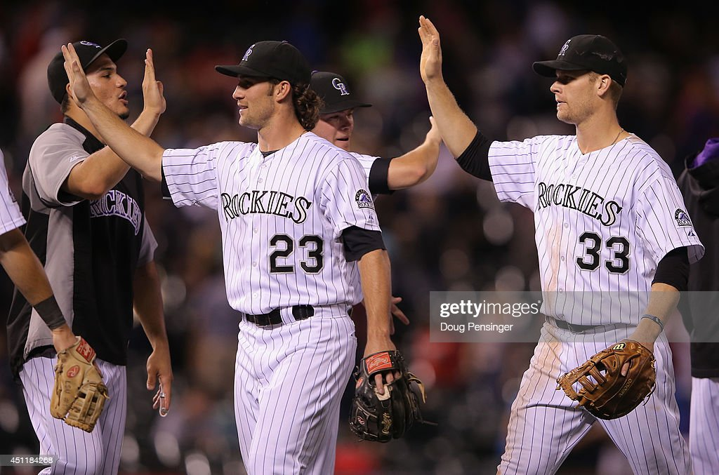 Charlie Culberson #23 of the Colorado Rockies and Justin Morneau #33 of the Colorado Rockies celebrate their 10-5 victory over the St. Louis Cardinals with their teammates Nolan Arenado #28 and Josh Rutledge #14 at Coors Field on June 24, 2014 in Denver, Colorado.