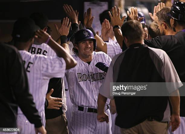Charlie Culberson of the Colorado Rockies celebrates his three run home run off of Alfredo Simon of the Cincinnati Reds to give the Rockies a 7-2...