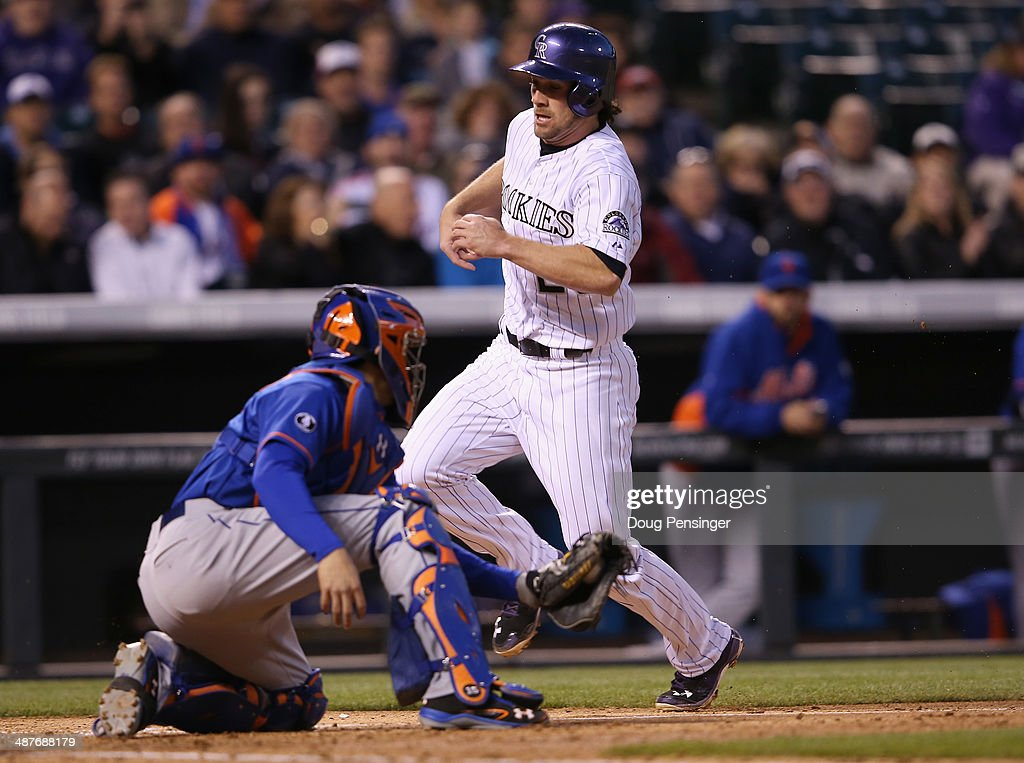 Charlie Culberson #23 of the Colorado Rockies scores as catcher Travis d'Arnaud #15 of the New York Mets takes the throw on a sacrifice fly by Nolan Arenado #28 of the Colorado Rockies to take a 6-0 lead in the fourth inning at Coors Field on May 1, 2014 in Denver, Colorado.