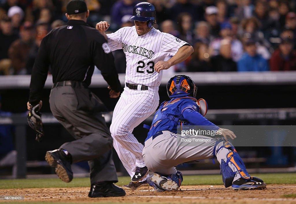 Charlie Culberson #23 of the Colorado Rockies scores as catcher Travis d'Arnaud #15 of the New York Mets takes the throw and umpire Will Little oversees the play on a sacrifice fly by Nolan Arenado #28 of the Colorado Rockies to take a 6-0 lead in the fourth inning at Coors Field on May 1, 2014 in Denver, Colorado.