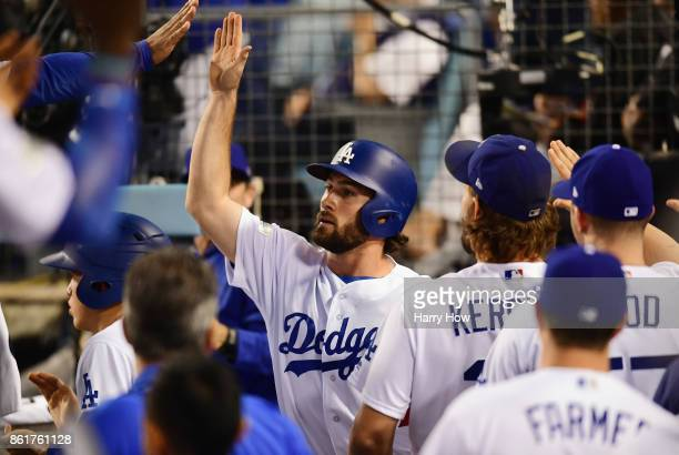 Charlie Culberson of the Los Angeles Dodgers celebrates with teammates in the dugout after scoring a run in the fifth inning against the Chicago Cubs...