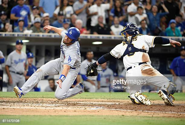 Charlie Culberson of the Los Angeles Dodgers scores ahead of the tag of Derek Norris of the San Diego Padres during the sixth inning of a baseball...