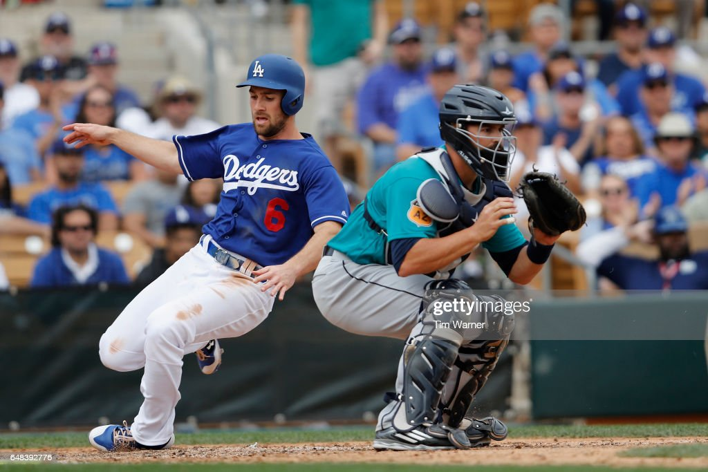 Charlie Culberson #6 of the Los Angeles Dodgers slides into home as Nevin Ashley #10 of the Seattle Mariners awaits the throw in the seventh inning of the spring training game at Camelback Ranch on March 5, 2017 in Glendale, Arizona.