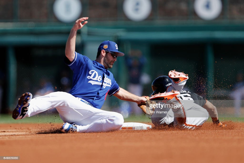 Charlie Culberson #6 of the Los Angeles Dodgers tags Gorkys Hernandez #66 of the San Francisco Giants for an out on a steal attempt in the first inning during the spring training game at Camelback Ranch on March 7, 2017 in Glendale, Arizona.