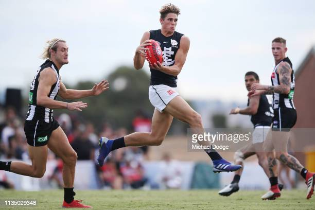 Charlie Curnow of the Blues gathers the ball against Darcy Moore of the Magpies during the 2019 JLT Community Series match between the Collingwood...