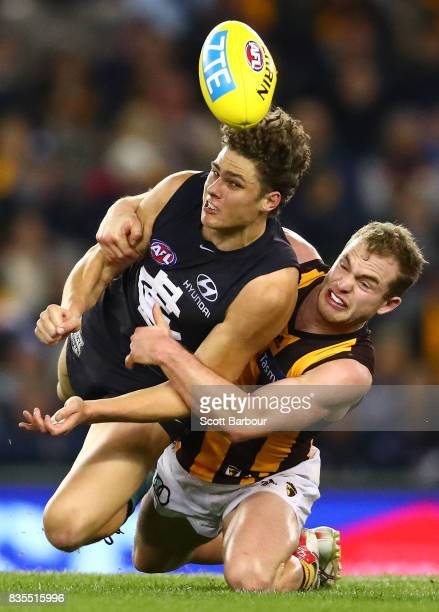 Charlie Curnow of the Blues is tackled by Tom Mitchell of the Hawks during the round 22 AFL match between the Carlton Blues and the Hawthorn Hawks at...