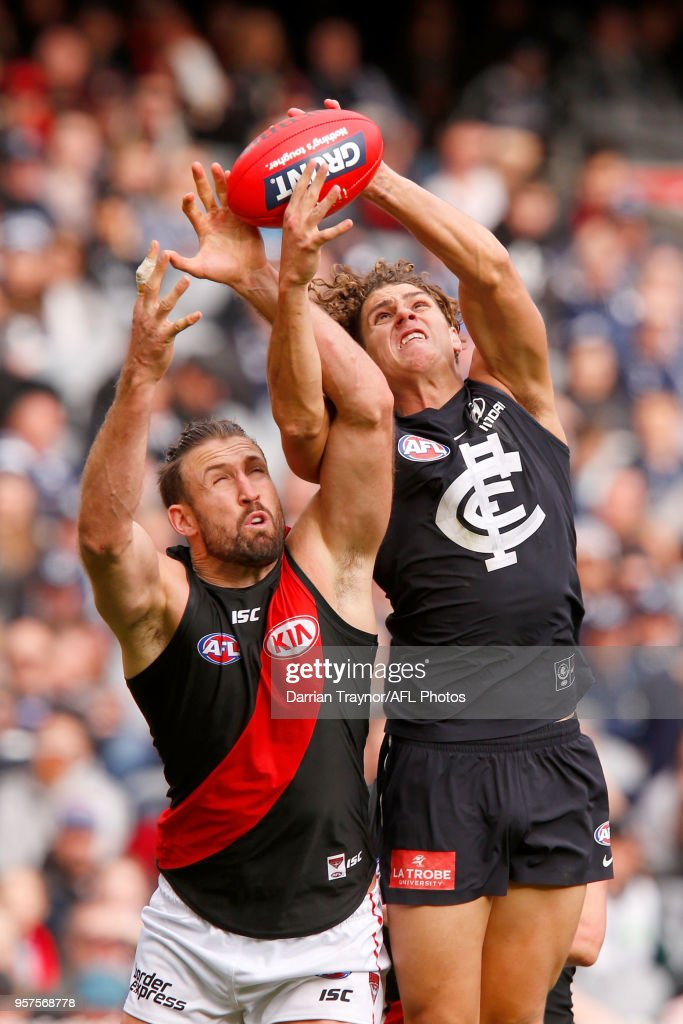 Charlie Curnow of the Blues marks in front of Cale Hooker of the Bombers during the round eight AFL match between the Carlton Blues and the Essendon Bombers at Melbourne Cricket Ground on May 12, 2018 in Melbourne, Australia.