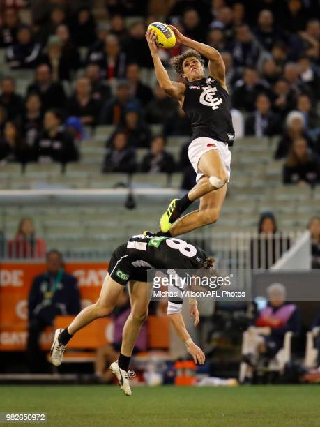 Charlie Curnow of the Blues takes a spectacular mark over Tom Langdon of the Magpies during the 2018 AFL round 14 match between the Collingwood...