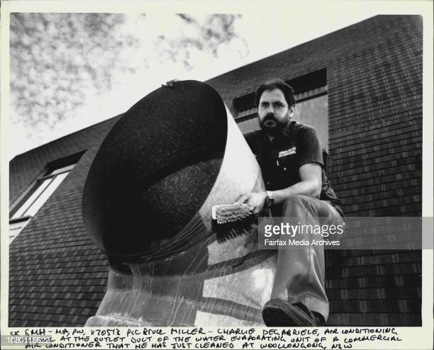 Charlie Degabriele air conditioning mechanic at the outlet duct of the water evaporating unit of a commercial air conditioner that he was just...