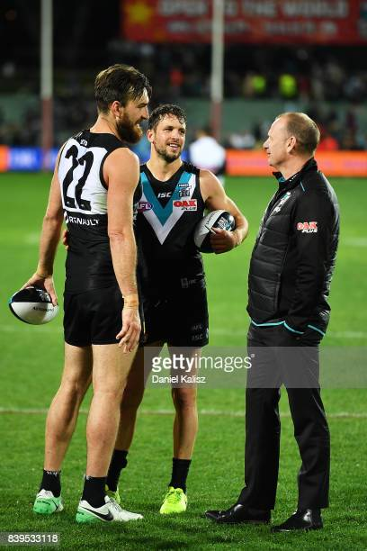 Charlie Dixon and Travis Boak of the Power chat with Ken Hinkley the coach of the Power after the round 23 AFL match between the Port Adelaide Power...