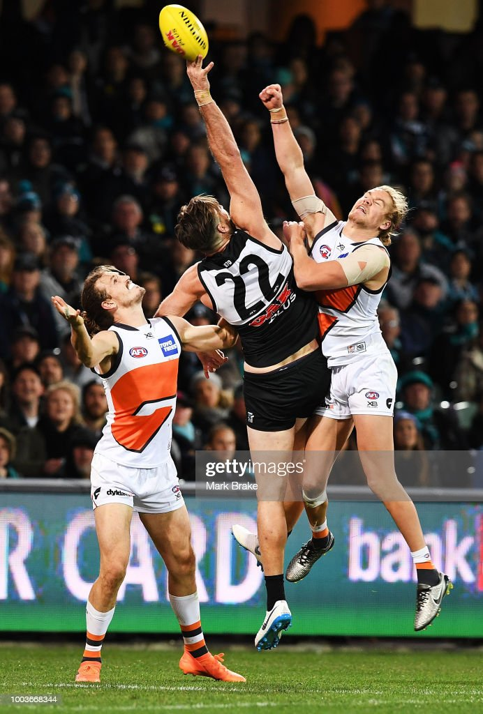 Charlie Dixon of Port Adelaide gets a hand to the ball between Phil Davis of the Giants and Harry Himmelberg of the Giants during the round 18 AFL match between the Port Adelaide Power and the Greater Western Sydney Giants at Adelaide Oval on July 22, 2018 in Adelaide, Australia.