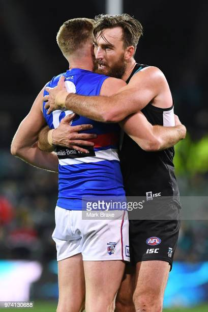 Charlie Dixon of Port Adelaide hugs former team mate Jackson Trengove of the Bulldogs after the round 13 AFL match between Port Adelaide Power and...