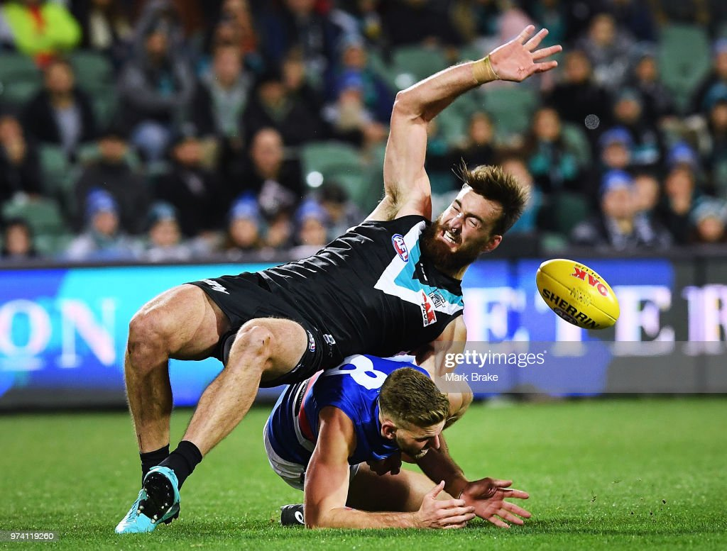 Charlie Dixon of Port Adelaide lands awkwadly on Jackson Trengove of the Bulldogs during the round 13 AFL match between Port Adelaide Power and the Western Bulldogs at Adelaide Oval on June 14, 2018 in Adelaide, Australia.