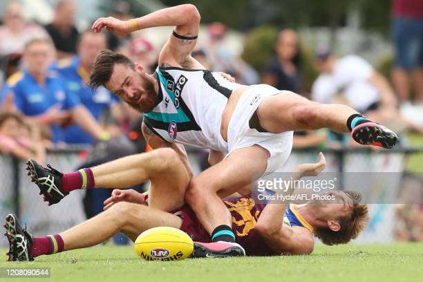 Charlie Dixon of the Power is tackled by Harris Andrews of the Lions during the 2020 Marsh Community AFL Series match between the Brisbane Lions and...