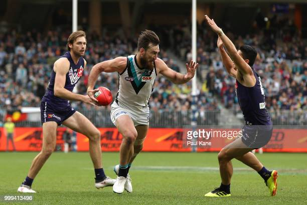 Charlie Dixon of the Power looks to fend off a tackle by Bailey Banfield of the Dockers during the round 17 AFL match between the Fremantle Dockers...