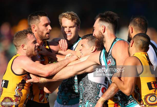 Charlie Dixon of the Power Tom Mitchell of the Hawks and Jack Watts of the Power wrestle during the round 11 AFL match between the Hawthorn Hawks and...