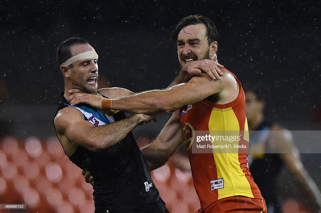 Charlie Dixon of the Suns wrestles with Matthew Broadbent of the Power during the round 22 AFL match between the Gold Coast Suns and the Port Adelaide Power at Metricon Stadium on August 29, 2015 on the Gold Coast, Australia.