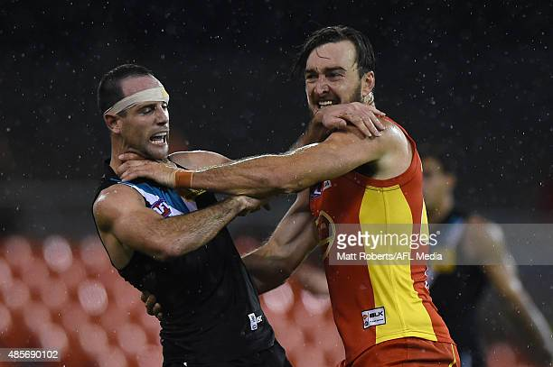 Charlie Dixon of the Suns wrestles with Matthew Broadbent of the Power during the round 22 AFL match between the Gold Coast Suns and the Port...
