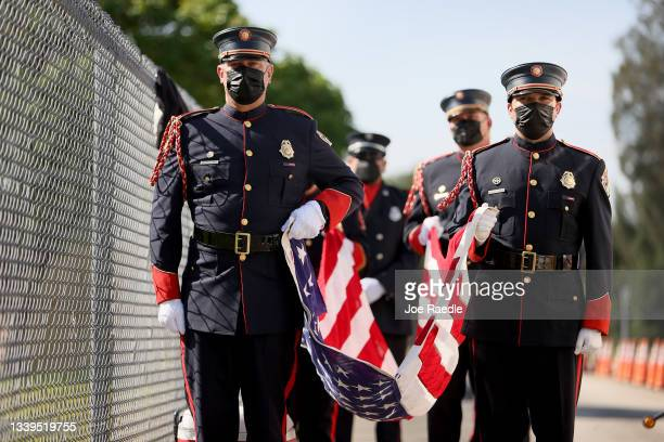 Charlie Eckert and Jorge Bittencourt from the Broward Fire Rescue Honor Guard help carry the American flag during a ceremony at Western High School...
