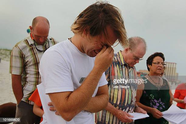 Charlie Green is overcome with emotion during a public prayer vigil for the oil spill along Pensacola Beach where oil globs have come ashore as oil...