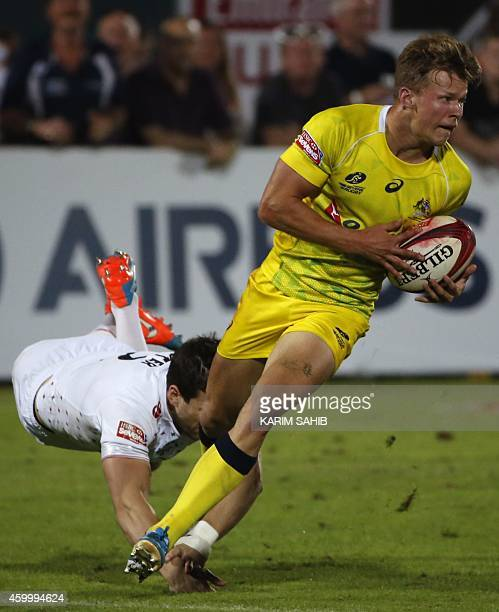 Charlie Hayter of England tries to tackle Cameron Clark of Australia during their rugby match in the first day of the Dubai leg of IRB's Sevens World...