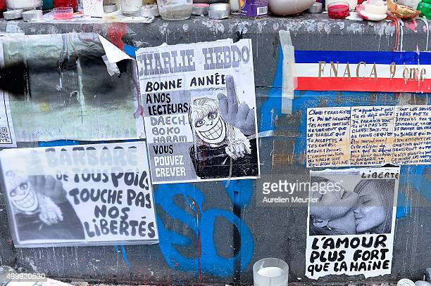 Charlie Hebdo sign saying 'Happy new year to our readers Daech and Boko Haram you can die' is seen at the bottom of the Place de la Republique statue...