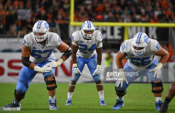Charlie Heck Antonio Williams and Billy Ross of the North Carolina Tar Heels line up against the Miami Hurricanes at Hard Rock Stadium on September...