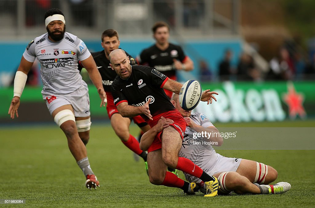 Charlie Hodgson of Saracens offloads under pressure from Geoffrey Fabbri of Oyonnax during the European Rugby Champions Cup match between Saracens and Oyonnax at Allianz Park on December 19, 2015 in Barnet, England.