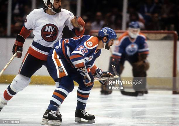 Charlie Huddy of the Edmonton Oilers skates on the ice as he is defended by John Tonelli of the New York Islanders during the 1984 Stanley Cup Finals...