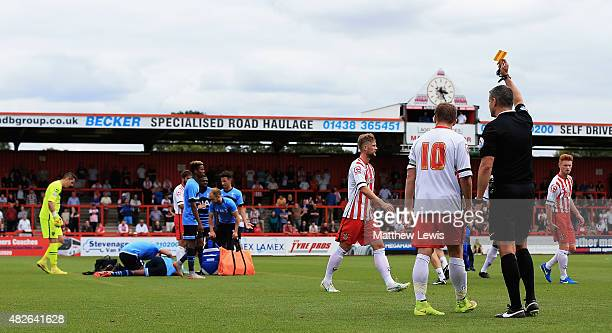 Charlie Lee of Stevenage is given a yellow card by referee Iain Williamson after his challenge on Nathan Oduwa of Tottenham XI during a preseason...
