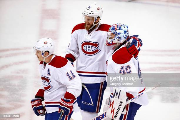 Charlie Lindgren of the Montreal Canadiens celebrates a 32 overtime win over the Detroit Red Wings with Brendan Gallagher and Brett Lernout at Joe...