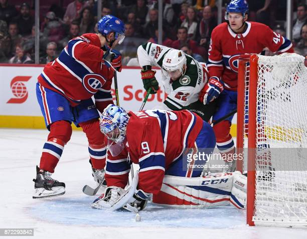 Charlie Lindgren of the Montreal Canadiens covers up the puck with help from teammates under pressure from Nino Niederreiter of the Minnesota Wild in...