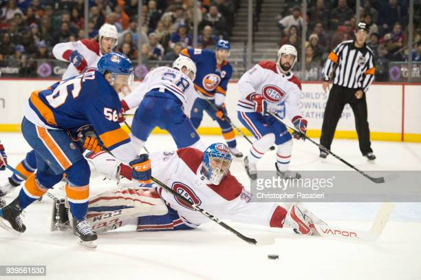 Charlie Lindgren of the Montreal Canadiens sprawls out to make a save against Tanner Fritz of the New York Islanders during the third period at...