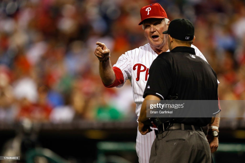 Charlie Manuel #41 of the Philadelphia Phillies speaks with umpire Dan Bellino #93 in the ninth inning of the game against the San Francisco Giants at Citizens Bank Park on July 30, 2013 in Philadelphia, Pennsylvania. The Phillies won 7-3.