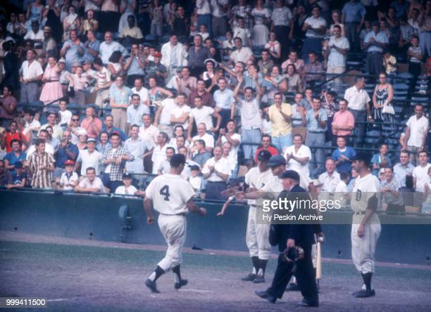 Charlie Maxwell of the Detroit Tigers is congratulated by teammates Eddie Yost Bobo Osborne and Don Mossi after hitting a homerun during an MLB game...