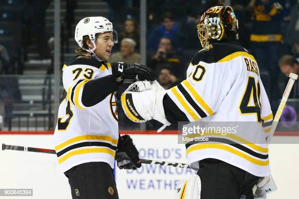 Charlie McAvoy and Tuukka Rask of the Boston Bruins celebrate a 51 against the New York Islanders at Barclays Center on January 2 2018 in New York...