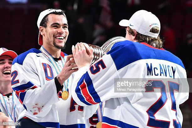 Charlie McAvoy hands over the IIHF trophy to teammate Jordan Greenway of Team United States during the 2017 IIHF World Junior Championship gold medal...