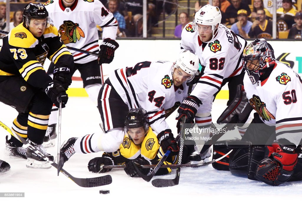 Charlie McAvoy #73 of the Boston Bruins and Anders Bjork #10 look for a shot on goal against Corey Crawford #50 of the Chicago Blackhawks during the third period of their preseason game at TD Garden on September 25, 2017 in Boston, Massachusetts. The Bruins defeat the Blackhawks 4-2.
