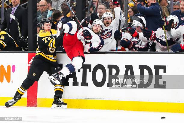 Charlie McAvoy of the Boston Bruins checks Josh Anderson of the Columbus Blue Jackets in Game One of the Eastern Conference Second Round during the...