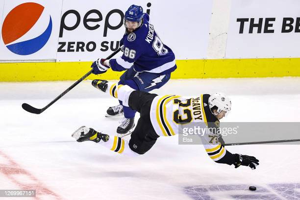Charlie McAvoy of the Boston Bruins gets tripped up against Nikita Kucherov of the Tampa Bay Lightning during the second period in Game Five of the...