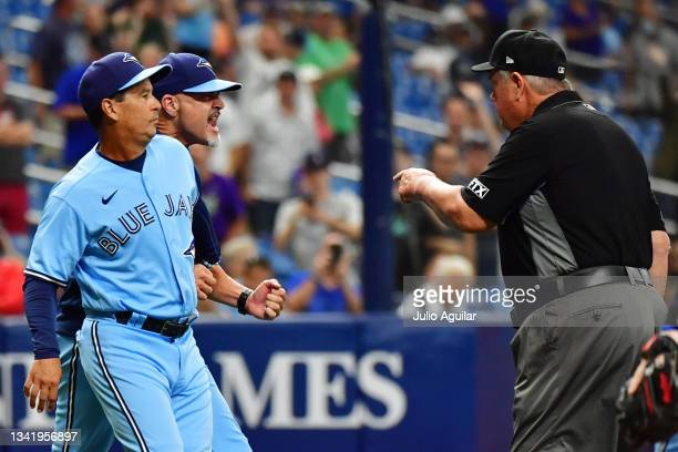 Charlie Montoyo holds Pete Walker of the Toronto Blue Jays back as umpire Joe West approaches during the eighth inning after Ryan Borucki hit Kevin...